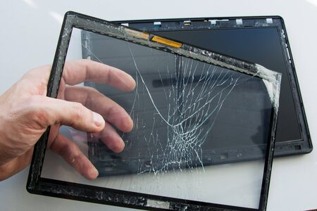 Cracked tablet computer with broken glass touch screen. A technician is fixing and replacing the broken screen on damaged gadget. Repair device in service center.
