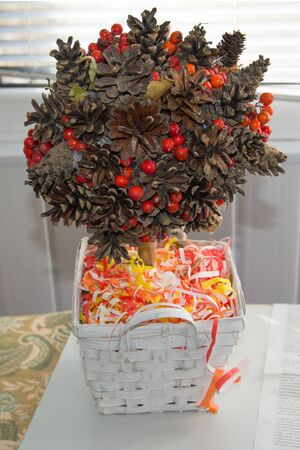 A festive fall arrangement. Composition Tree of fir and pine cones, Rowan berries, red, yellow and white curly ribbons of paper in a white basket.