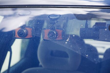 Three dashboard camera mounted on the dirty front windshield. Car Camera DVR Dash Cam for safety on the road accident. View from outside the car