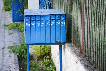 old retro blue mailbox on city street.