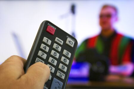 A man watches cable TV and switches TV channels with a remote control Archivio Fotografico