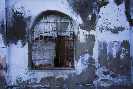 old boarded-up prison window with iron bars, prison wall.