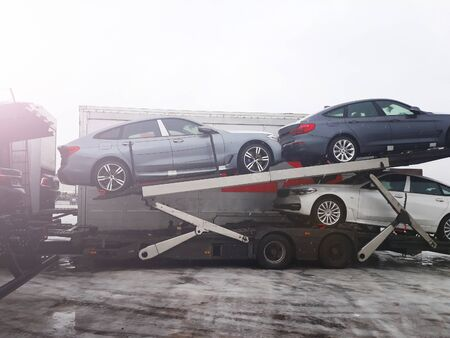 Loading new cars from conveyor of automobile plant on the truck for delivery to customers. Winter sunnyday is wet snow. The trailer transports cars on highway. Logistics company carrier delivers the goods to the customer. Stok Fotoğraf