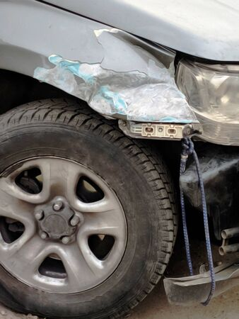The front bumper and the wing of a broken car. Front of silver car get damaged by crash accident on the road. Bumper tied with rope. Car repair or insurance concept. Blurred view of Damaged Auto.