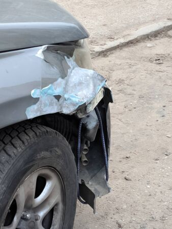 Front of silver car get damaged by crash accident on the road. The wing of a broken car. Bumper tied with rope. Car repair or insurance concept. Defocused, Blurred view of Damaged Car.