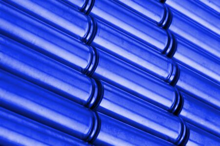 Angled view of blue metal parts with shiny steel cylindrical surface closeup. Abstract Industrial background with selective focus Stockfoto