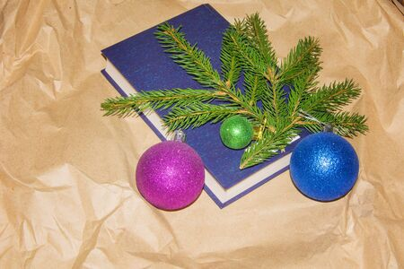 Colorfull Christmas ball, branch of spruce tree and blue book on gray table. Happy New Year decoration. Banco de Imagens