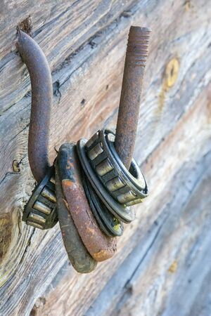 Many old rustic weathered large roller with ball bearing on iron hook, dried out grease and broken bearing. Industrial background texture metal fasteners and mechanical elements. Stock Photo