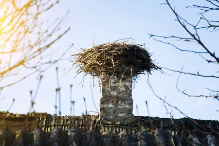 The European white stork empty nest is made of a lot of branches and and garbage, lies on a old brick chimney. Selective soft focus.