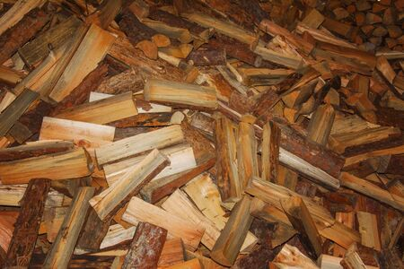 Chopped wood prepared for the winter heating season. A pile of firewood. Texture to Chop wood.