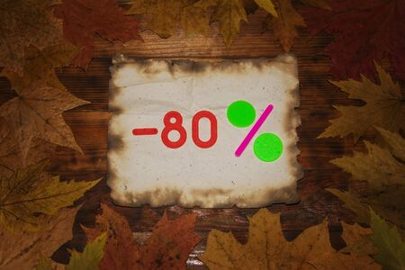 Autumn Sale 80 Percent Discount. The inscription on a piece of burned paper on a dark wooden background in a frame of colorful autumn leaves. Top view.