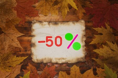 Autumn Sale 50 Percent Discount. The inscription on a piece of burned paper on a dark wooden background in a frame of colorful autumn leaves. Top view. Zdjęcie Seryjne