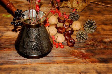 Autumn composition. Clay turka, pine cones, berries, walnuts, chestnuts on wooden Dark rustic background. Banco de Imagens