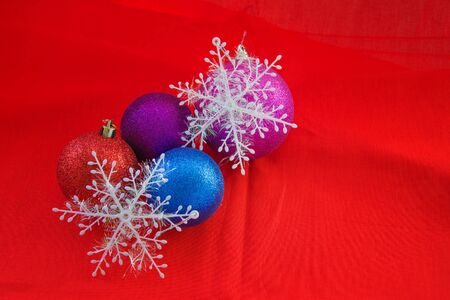 Set of red, blue, purple baubles and white snowflakes decoration on red background with copy space. New Year greeting card.