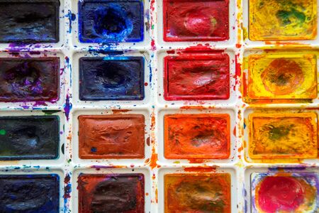 Palette with used watercolors paintbox. Paintings art concept. Painting hobby. Back to school. Top view. Copy space.
