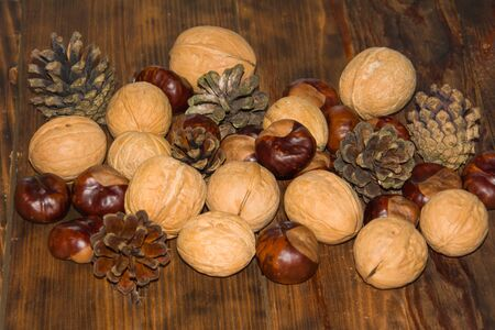 Autumn composition. Pine cones, walnuts, chestnuts on wooden Dark rustic background.