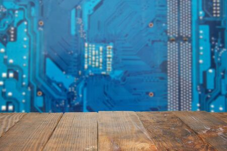 Empty dark rustic wood table with blurred abstract blue background electronic printed circuit board for montage product. Electronic and computer technology. Surface for display or design product.