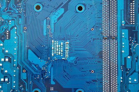 Printed circuit boards of computer motherboard close-up. Electronic and computer technology. Technology of scientific knowledge, electronics repair, information recovery. Yellow background. Selective soft focus.