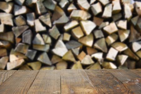 Empty dark rustic wood table with blurred abstract of stacked up, chopped firewood logs in a pile. A lot of firewood outdoor, brown background. Surface for display or design product. Banco de Imagens