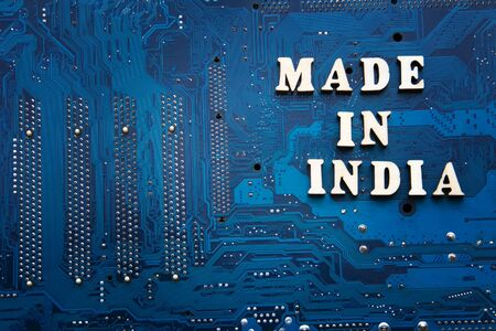 Inscription Made in India on a blue printed circuit board background. Copyspace for design. Label made in India electronics manufacturing concept Reklamní fotografie