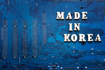 Made in korea. Inscription on a blue printed circuit board background. Copyspace for design. Korea electronics manufacturing concept