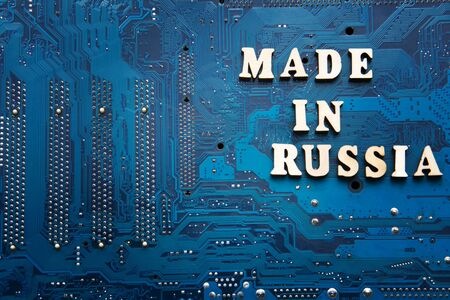 Made in Russia. Inscription on a blue printed circuit board background. Russia electronics manufacturing concept. Foto de archivo
