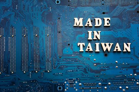 Inscription Made in Taiwan on a blue electronic printed circuit board. Background with copyspace for design. Taiwan electronics manufacturing concept