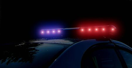 Blurred defocused silhouette of road police patrol car on the street of city at night. Flashing red and blue police car led lights in night time. The roof-mounted lightbar alarm emergency lighting siren in darkness. Foto de archivo