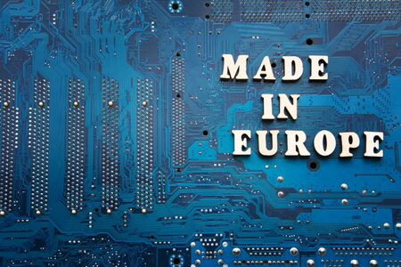 Made in Europe. Inscription on a blue printed circuit board background. Copyspace for design.