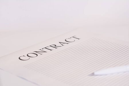 Contract paper and pen on white desk background. Focus on title Contract. Defocused pencil