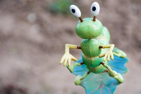 Funny Green Caterpillar on leaf in garden. Decorative plug Фото со стока