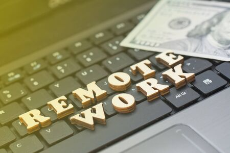 The inscription remote work against the background of a working laptop and money. The concept of working through the Internet Фото со стока