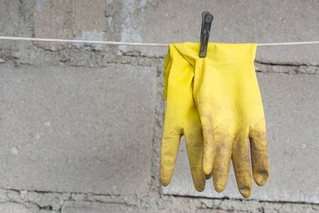 Dirty yellow used medical rubber gloves on the rope with clothespin on concrete background