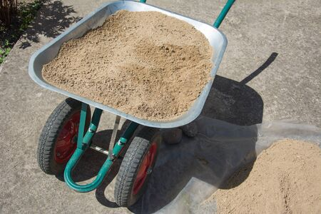 Dirty green wheelbarrow full of sand. Handcart standing in the construction site or household