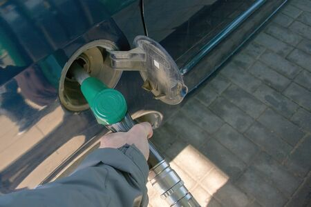 A man's hand holds a green refueling gun. Filling gun inserted into the hole of a empty gasoline tank of a car on a diesel fueling