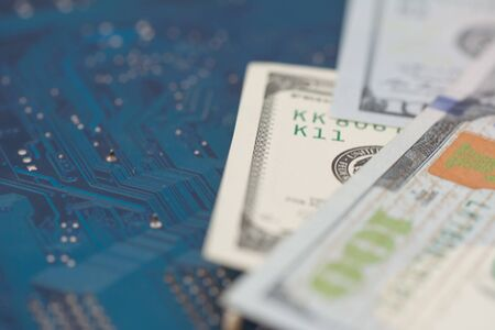 Business money dollar on PCB circuit board technology. Business concept of world digital money and remote job. Selective focus