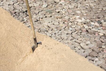 Shovel for scoop sand in construction work, sand material and stones for construction work. Building materials. Preparing to fill the Foundation for the construction of a residential building