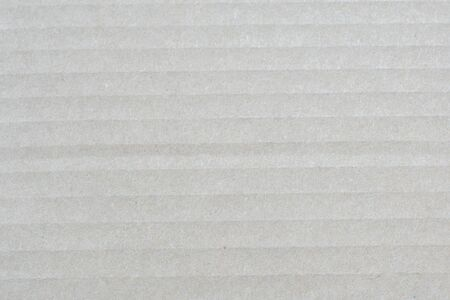 Brown corrugated cardboard paper texture with horizontal stripes. Closeup of brown textured surface for background