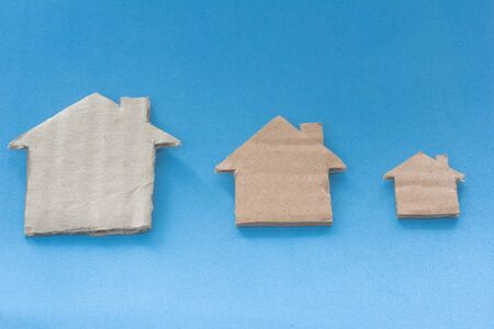 Different Size Of Houses Arranged In Row on blue background. Three differently sized cardboard models of houses. Rent, purchase, delivery of housing and real estate concept Фото со стока