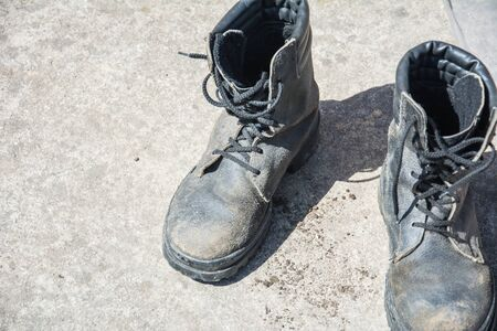 Old Black Leather army boots. Military boots of soldiers standing on the cement ground Фото со стока