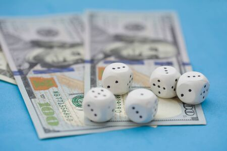 Game dice and hundred dollar bills on blue background. Board game, gambling, casino concept