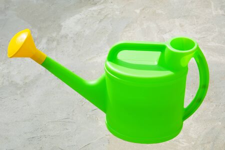 Green plastic watering can with yellow nozzle on gray concrete background. Watering pot is the simplest tool for drip irrigation.
