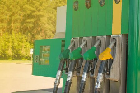 Gas station with the rays of the sun. Colorful petrol pump filling nozzles. Fuel oil gasoline dispenser at petrol filling station