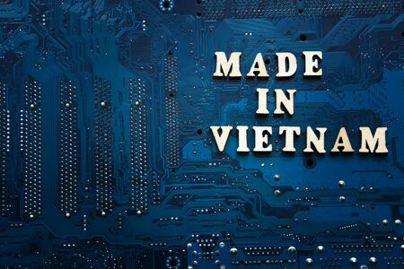 Text Made in Vietnam on a blue electronic printed circuit board. Vietnam electronics manufacturing concept. Background with copyspace for design. Фото со стока