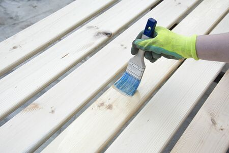 Woman Hand with a brush varnishes old wooden boards. Paint Brush preparation to stain the wood slats. Worker paint with brush a wood wall from boards in construction site Фото со стока