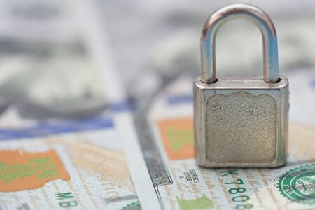 Iron lock key on 100 US dollars banknote background. Money stack for safety and investment. Saving and financial security concept Фото со стока - 148832089