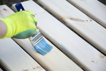 Woman Hand in glove with a brush varnishes old wooden boards. Worker paint with brush a wood table from boards in construction site