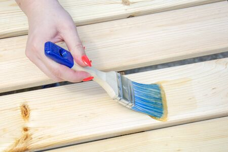 Woman with a beautiful manicure paints wall wooden boards with a brush. Concept of repair, construction or House improvement diy