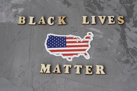 Black Lives Matter flat lay on a gray background with american flag. Fight against racism concept