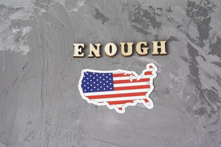 Enough sign flat lay on a gray background with american flag. Concept of racism. Discrimination, racial problems Фото со стока
